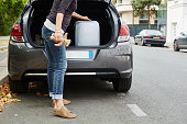 Woman standing beside car, putting suitcase in open boot