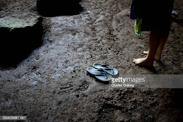 Woman standing beside flip-flops on muddy ground, low section