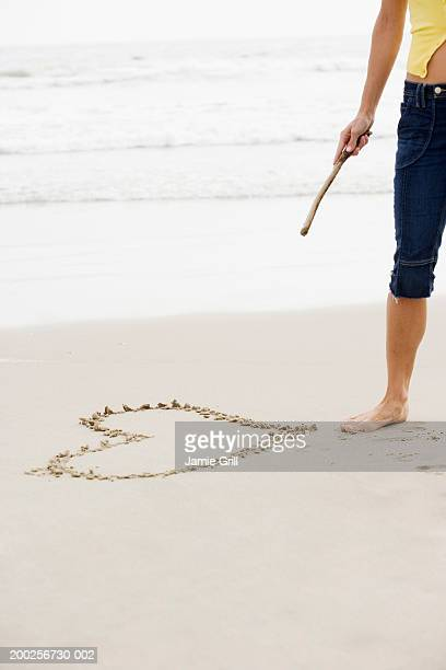 Woman standing beside heart drawn on beach, holding stick, mid section