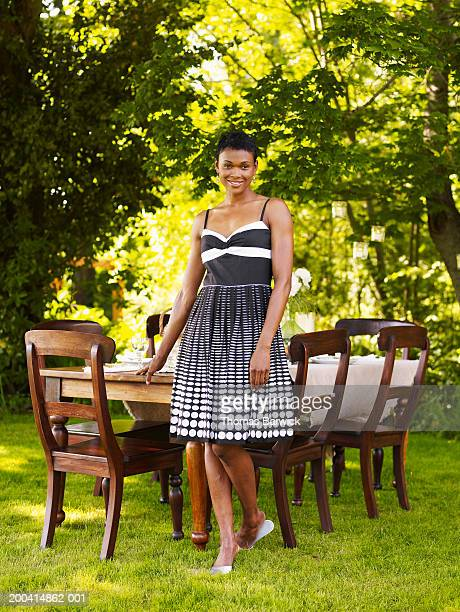 Woman standing beside outdoor dining table, smiling, portrait