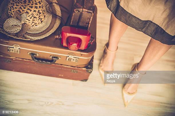 Donna in piedi dietro le valigie