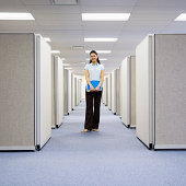 Woman standing between office cubicles, holding file, smiling