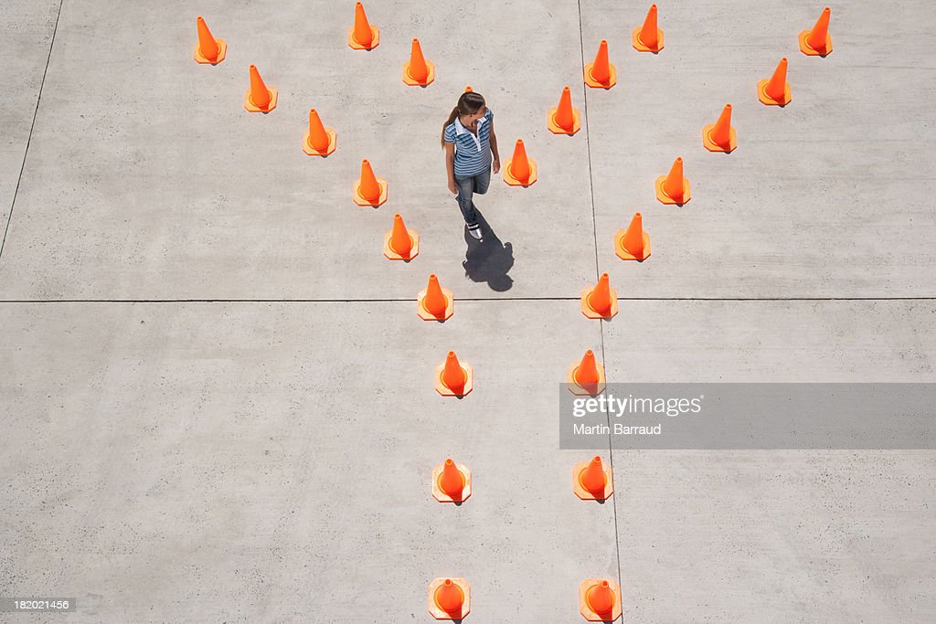 Woman standing between rows of traffic cones : Stock Photo