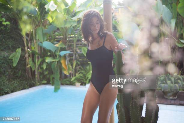 Woman standing by a swimming pool in a tropical villa