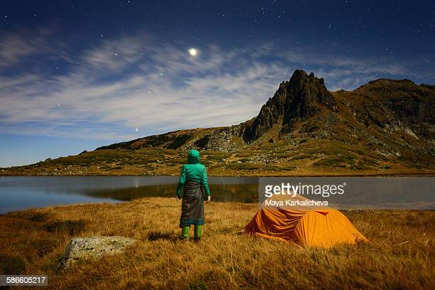 Woman standing by a tent at night in a mountain