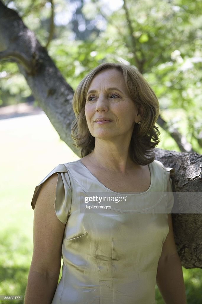 Woman standing by a tree : Stock Photo