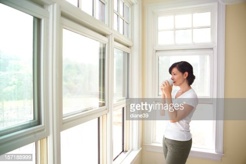 woman standing by a window drinking coffee