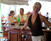 Woman standing by bar on ship