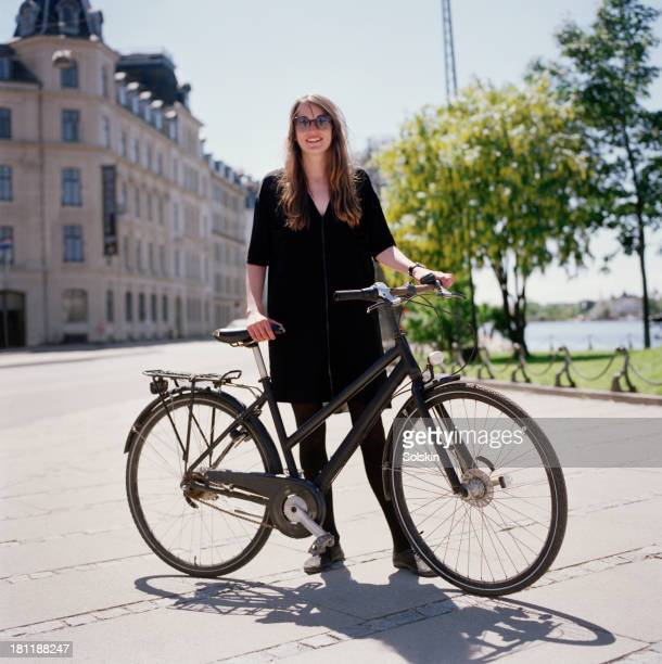 woman standing by bicycle in city area