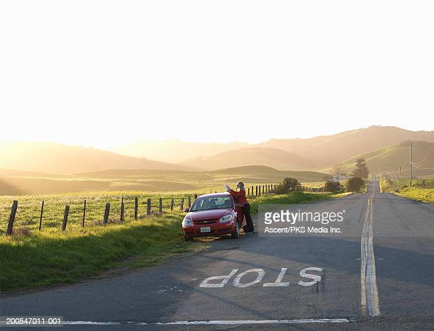 Woman standing by car on roadside reading map