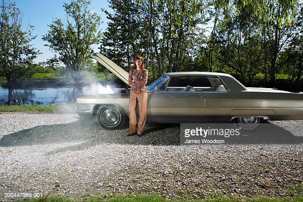 Woman standing by car with steaming engine on track by lake