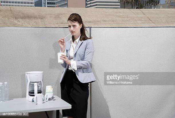 Woman standing by coffeemaker holding cup in office set up on construction site