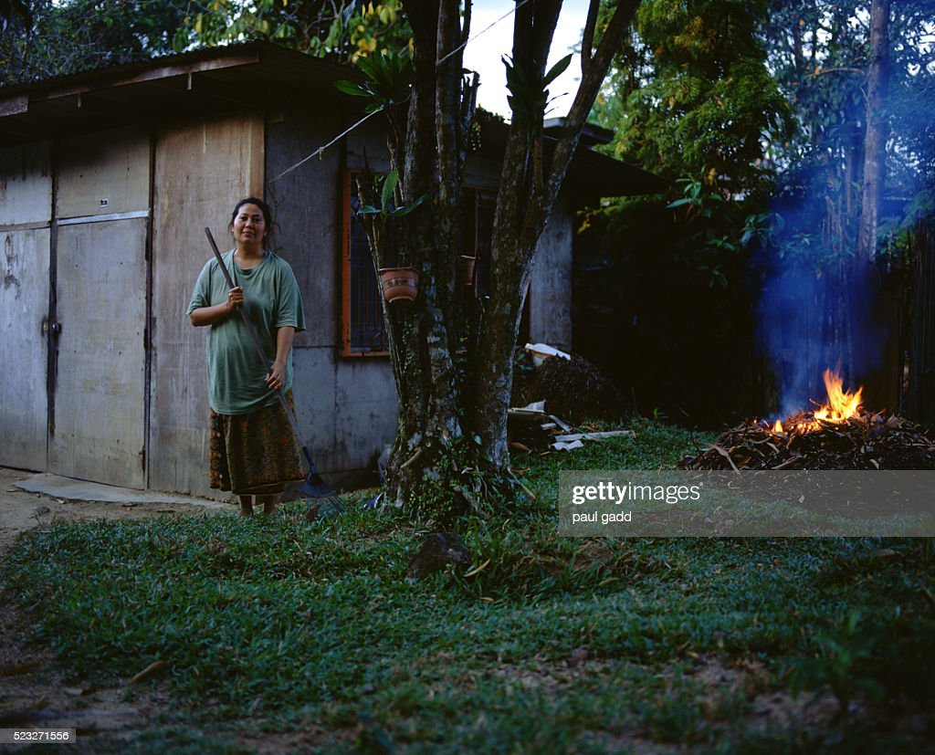 woman standing by house near burning yard waste stock photo