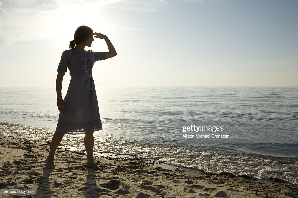 Woman standing by ocean : Stock Photo