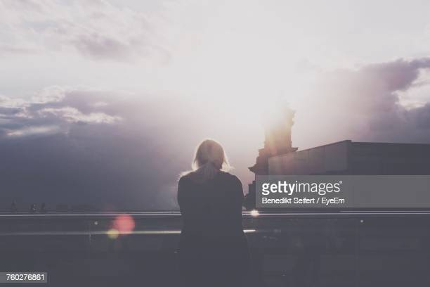 Woman Standing By Railing In City Against Sky