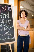 Woman standing by sign in cafe