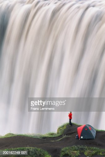 Woman standing by tent, looking at waterfall : Stock Photo