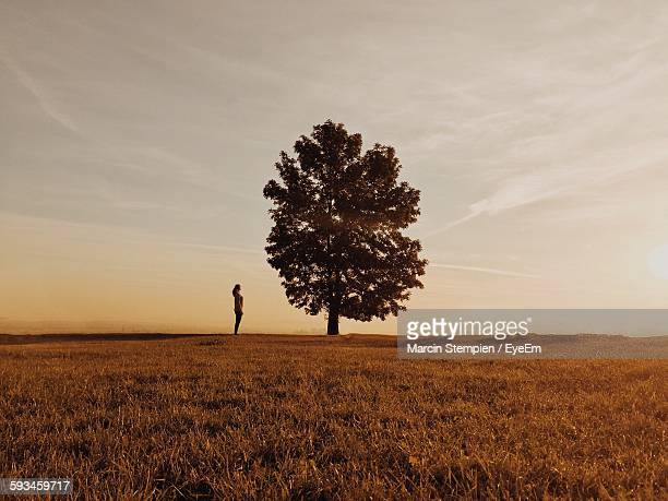 Woman Standing By Tree On Grassy Field Against Sky During Sunset
