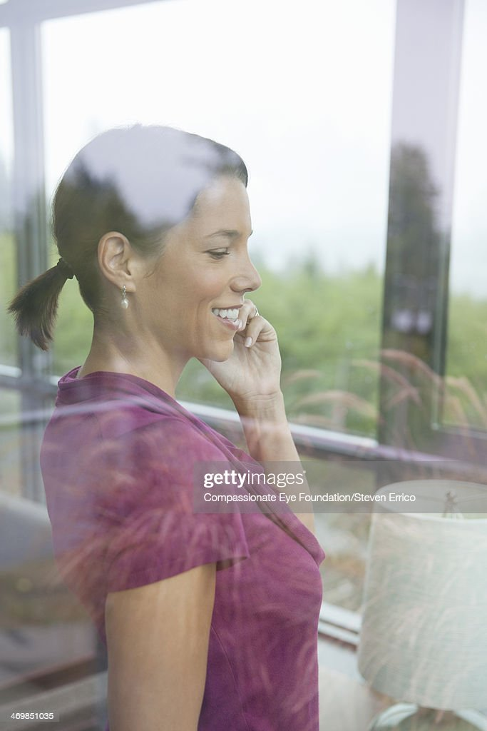Woman standing by window talking on cell phone : Stock Photo