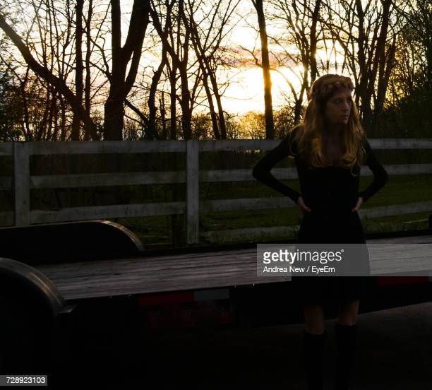 Woman Standing By Wooden Fence On Field