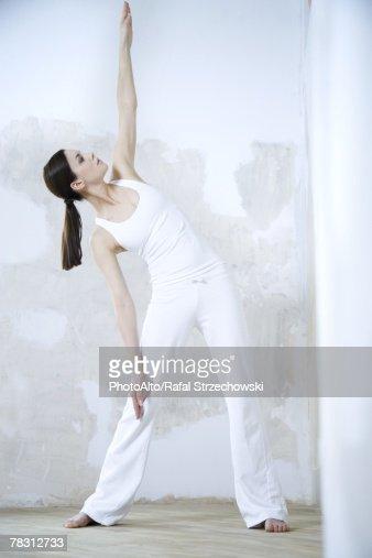 Woman standing, doing yoga pose, full length