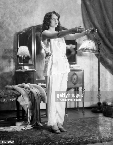 Woman Standing Exercising In Bedroom Wearing Pajamas Arms Stretched Out Mirror Vanity Lamp In Background Sleepwalking.