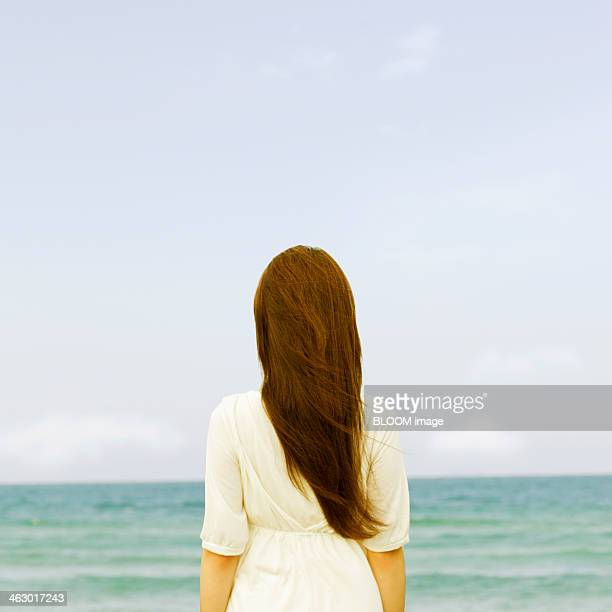 Woman Standing Facing The Sea