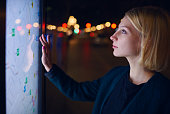 Gorgeous young female touching sensitive display of modern smart city bus stop for check her location into the night