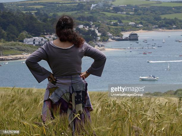 Woman standing in a corn field looking at the view Cornwall UK