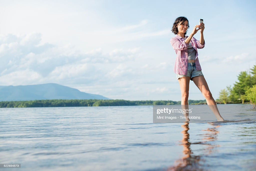A woman standing in a lake in summer. Taking a photograph.