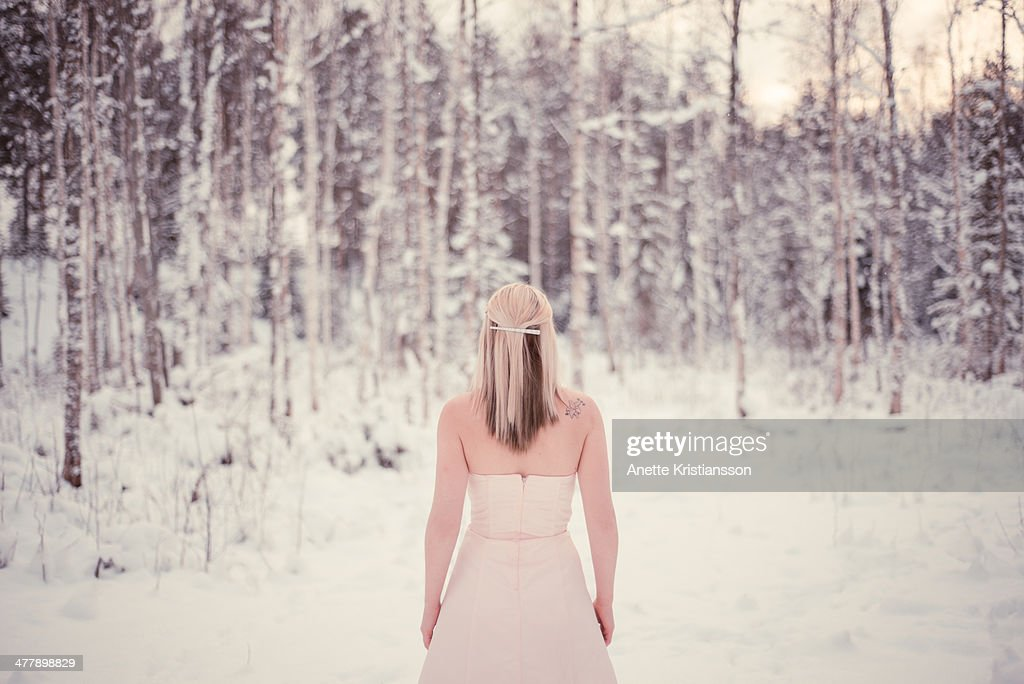 Woman standing in a snowscape dressed in a gown