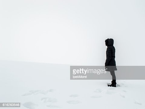 Woman standing in a snowy field : Stock Photo