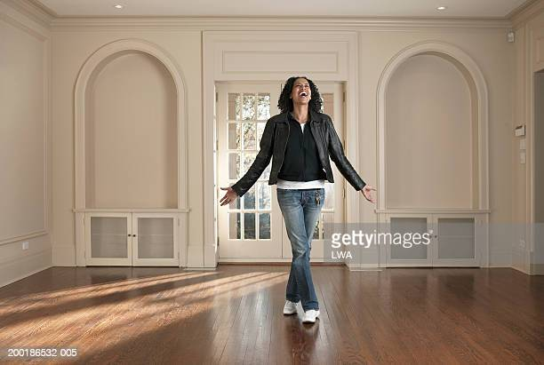 Woman standing in barren room, arms outstretched, smiling