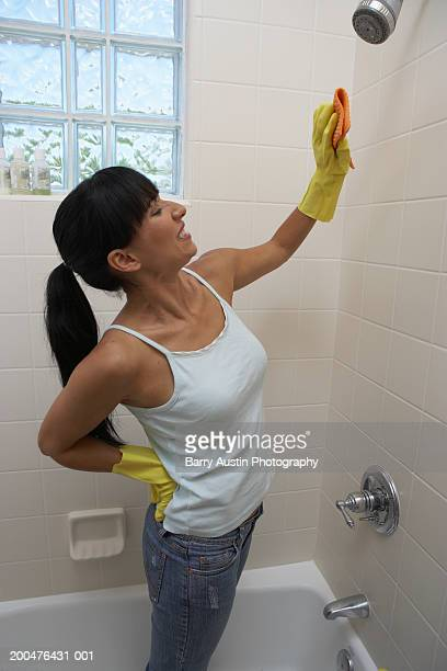 Woman standing in bath cleaning bathroom tiles, smiling
