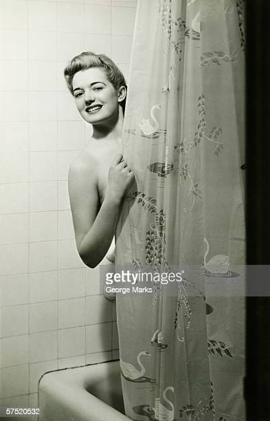 Woman standing in bathtub, peering through shower curtain, (B&W), portrait