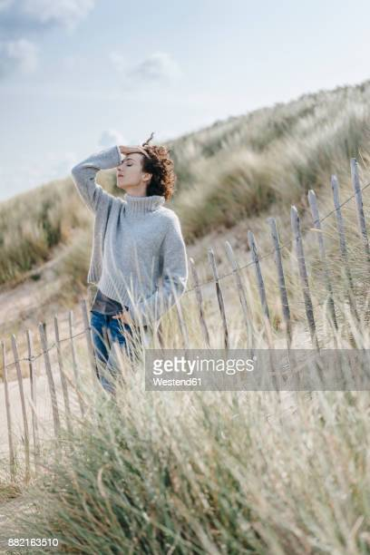 Woman standing in beach dune