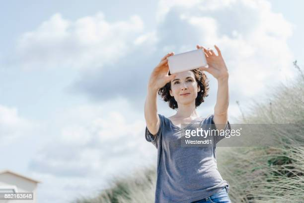 Woman standing in beach dune taking a selfie