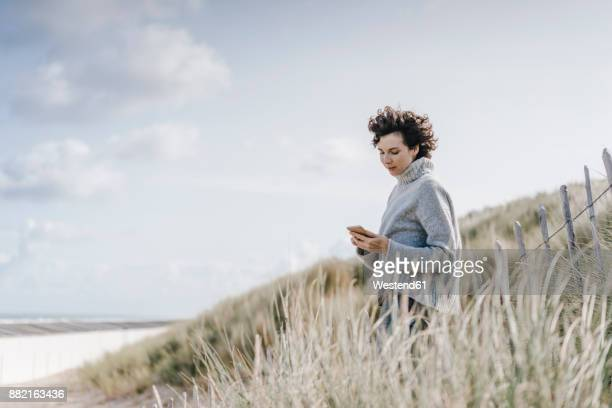 Woman standing in beach dune using cell phone