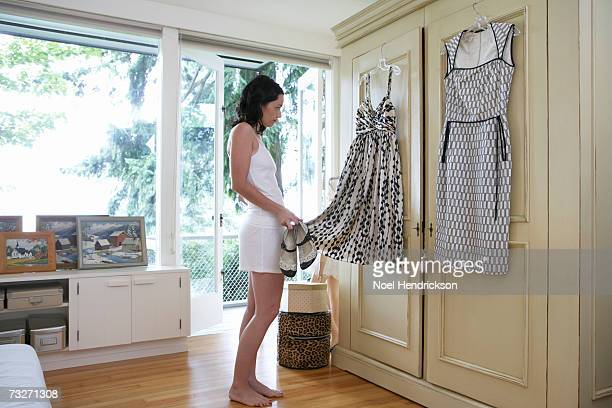 Woman standing in bedroom, choosing dress