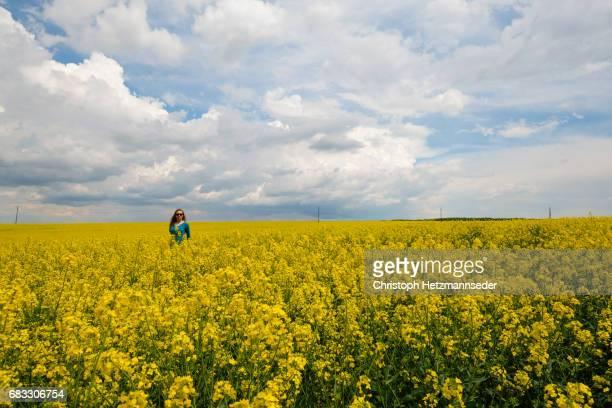 Woman standing in canola field