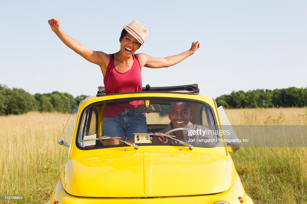Woman standing in car sun roof in field : Stock Photo