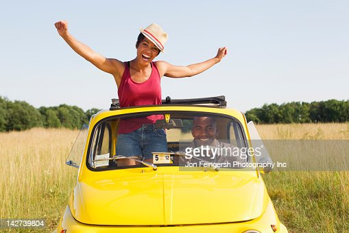 Woman Standing In Car Sun Roof In Field Stock Photo