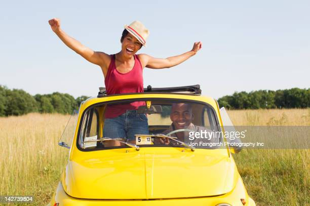 Woman standing in car sun roof in field