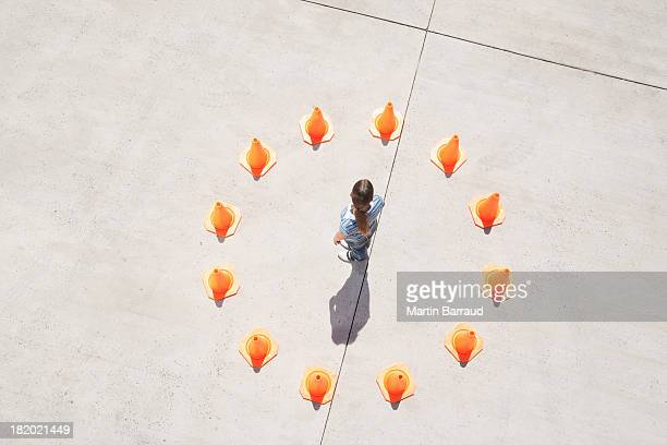 Woman standing in circle of traffic cones