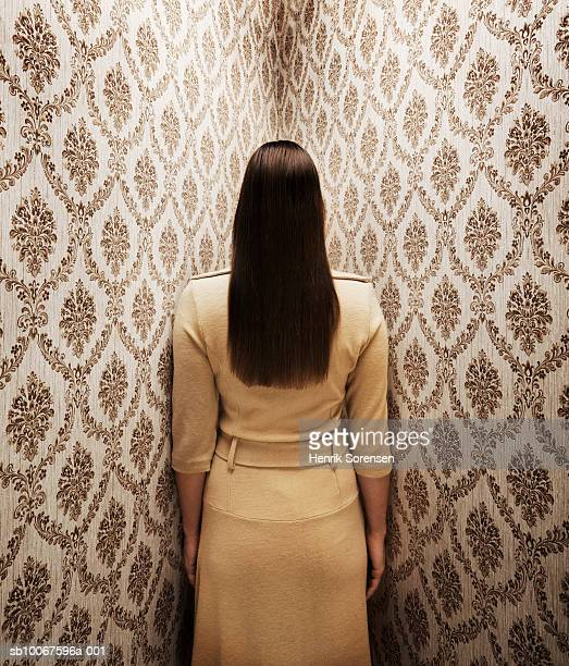 Woman standing in corner facing walls, rear view