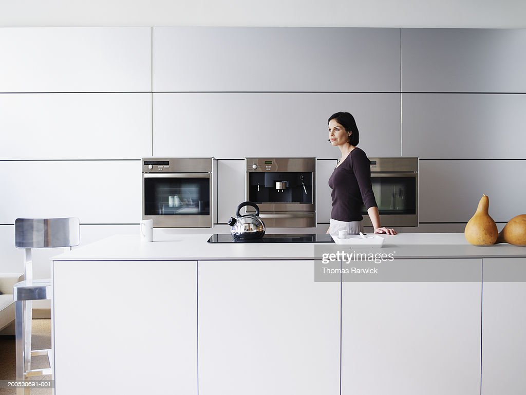 Kitchen Side View : Woman standing in domestic kitchen side view stock photo