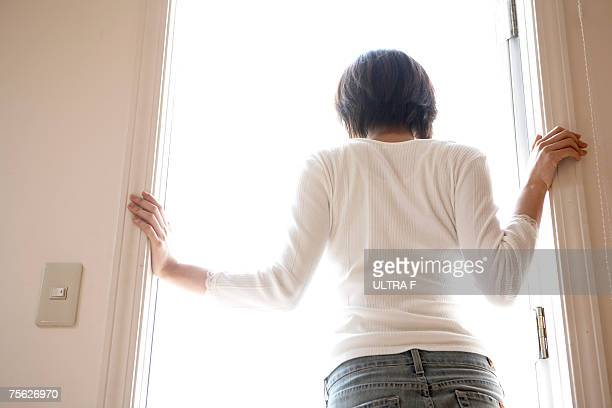 Woman standing in doorway of home, rear view