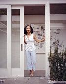 Woman standing in doorway of house, portrait