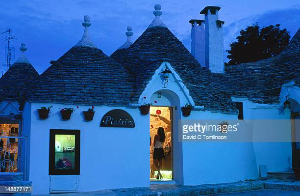 Woman standing in doorway of shop in 'trulli' district at dusk.