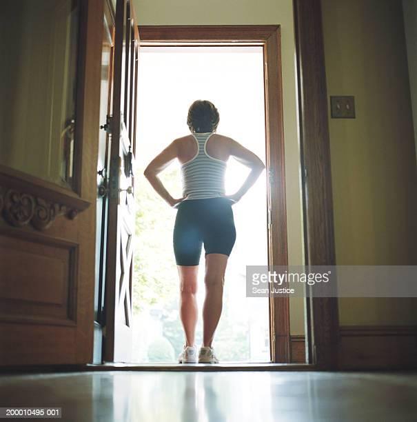 Woman standing in doorway, rear view